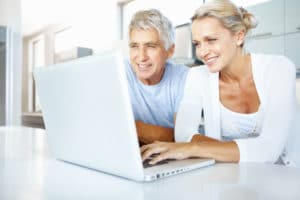 Senior man and mature woman using a laptop in the kitchen